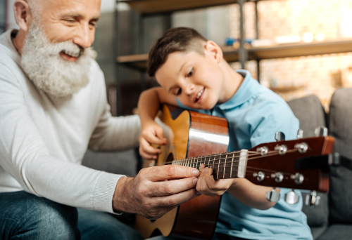 Instructor and boy play guitar