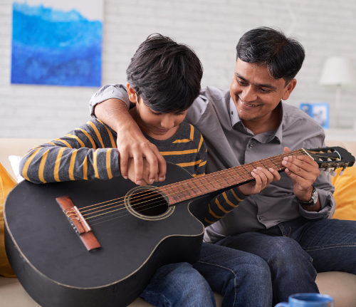 Dad helps son with guitar